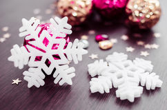 White snowflakes on background of magenta and gold xmas baubles. Royalty Free Stock Photos