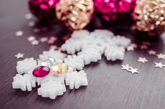 White snowflakes on background of magenta and gold xmas baubles. Royalty Free Stock Images