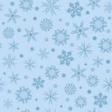 White snowflakes on a blue background. Stock Photos