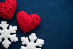 White snowflakes and red wool hearts on blue canvas background. Merry christmas card. Royalty Free Stock Photos