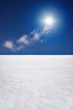 White snowy field with sun and blue sky Stock Photography