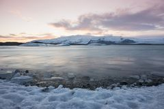White snowy mountain on Svalbard, Norway. Ice in ocean, twilight. In North pole. Pink clouds with ice floe. Beautiful landscape cold nature royalty free stock images