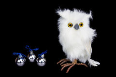 White snowy owl figurine with silver christmas balls. Isolated on black background royalty free stock images