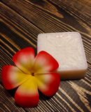 White soap on wooden background. White soap with frangipani on wooden background Stock Images