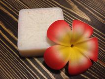 White soap on wooden background. White soap with frangipani on wooden background Stock Image