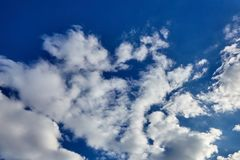 White soaring clouds on a blue sky background. White fluffy soaring clouds on a blue sky background royalty free stock photo