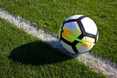 White soccer ball in the gate on a green grassy football field Royalty Free Stock Image