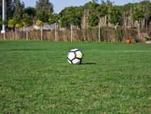 White soccer ball on a green grassy football field Royalty Free Stock Photos