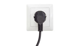 White socket outlet with connected corresponding power plug. White socket outlet European standard with connected corresponding black AC power plug closeup on a stock photography