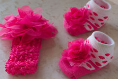 White socks in pink polka dots. And a flower for the baby on the table Royalty Free Stock Photo