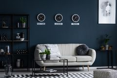 White sofa, coffee table, metal shelf with decorations and three. Clocks on the blue wall in living room interior stock image