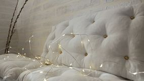 A white sofa with cushions is decorated with holiday lights.Christmas decorations for celebration stock footage