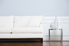 White Sofa and Glass End Table Against Blue Wall. White sofa and glass end table with vases set against pale blue wall. Horizontal shot Stock Photography