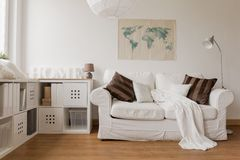 White sofa in living room. White sofa and commode in cozy living room Royalty Free Stock Image