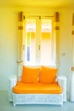 White sofa with orange cushion in the bedroom. White sofa with orange cushion in the bedroom, window and curtain Royalty Free Stock Photo