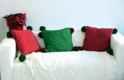 White sofa, three pillows, a flower pot.  stock image