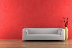 White sofa and vase in front of red wall