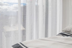 White soft bed and transparency curtain with buildings and blue. Partial view of white soft bed and transparency curtain with tall buildings and blue sky visible Stock Photos