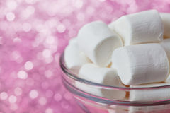 White soft marshmallows in glass bowl with pink bokeh background Stock Photo