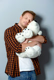 White and soft teddy bear in arms of a man. Portrait of relaxed boy hugging teddy bear alone in studio Stock Photo