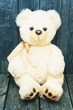 White soft teddy bear on a wooden background. White soft teddy bear sitting on a wooden background stock photography