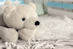 White soft toy bear. In a children's room stock photos