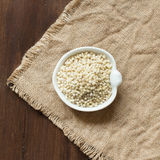 White Sorghum grain. In a bowl on burlap background Stock Images