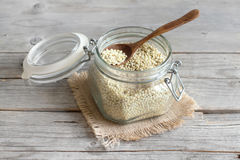 White Sorghum grain in a glass jar. On wooden table Royalty Free Stock Images