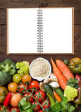 White sorghum grain with vegetables and notebook. White sorghum grain in a bowl with vegetables and notebook on wood stock images