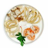 White soup with seafood, calamari, shrimp and fish in a plate on a white background. White soup with seafood, calamari, shrimp and fish on a white background Stock Images