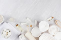 White spa cosmetics products and light bath accessories on white wood background, border, top view. Royalty Free Stock Image