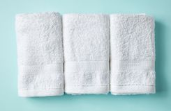 White spa towels on blue, from above. White spa towels on light blue background, top view stock images