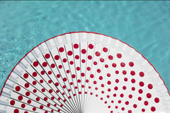 White spanish fan with red dots and swimming pool water behind Stock Images