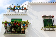 White Spanish house with balconies and plants. Zuheros is one of the Andalusian pueblo blancos with chalk white walls, where people decorate their houses with royalty free stock photo