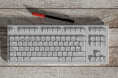 White spanish keyboard and red marker on wooden table Royalty Free Stock Images