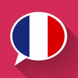 White speech bubble with France flag on pink background. White speech bubble with France flag and long shadow on pink background. French language conceptual Stock Photography