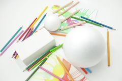 White spheres and prism with colored pencils and abstract paints on white background. Disordered materials, fun colors, children`s painting classes royalty free stock photography