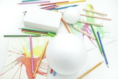 White spheres and prism with colored pencils and abstract paints on white background. Disordered materials, fun colors, children`s painting classes royalty free stock images