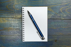 Spiral notebook with pen on old blue wooden table Stock Photo