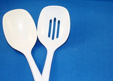 White spoons. Two white plastic kitchen spoons Royalty Free Stock Images