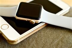 White Sport Band Silver Apple Watch on Gold Iphone 5s Stock Photography