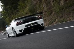 White Sport Car on mountain road. Fast White Sport Car on empty asphalt mountain road with space for text logos and products. Ferrari f430 challenge royalty free stock image