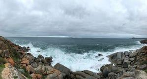White spray, rocky coast, white clouds stock photo