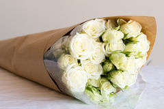 White spray roses in brown paper. White spray roses wrapped in clear cellophane and brown paper and lying on white tablecloth Stock Image
