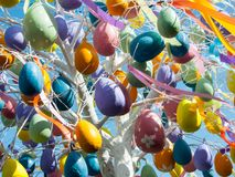 White spring tree decorated with multicolored eggs and ribbons on a blue sky background Royalty Free Stock Images