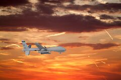Free White Spy Unmanned Drone Flies Against On Background Of Beautiful Sunset Sky Is Orange With Clouds And Condensation Traces Royalty Free Stock Images - 170203949