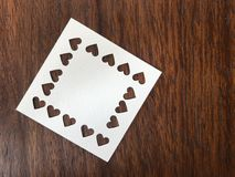 White square blank paper which was punched in heart shape on dark brown wood table stock photos