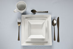 White, square dinner set with cutlery. Stock Photos