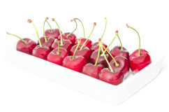 White square dish arranged with big ripe cherry berries Stock Image