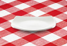 White square empty plate on red gingham tablecloth. White square empty plate on red  gingham tablecloth Royalty Free Stock Photography